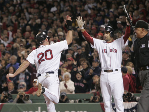 Kevin Youkilis (20) and Mike Lowell (right) celebrated the Red Sox first run of the game.