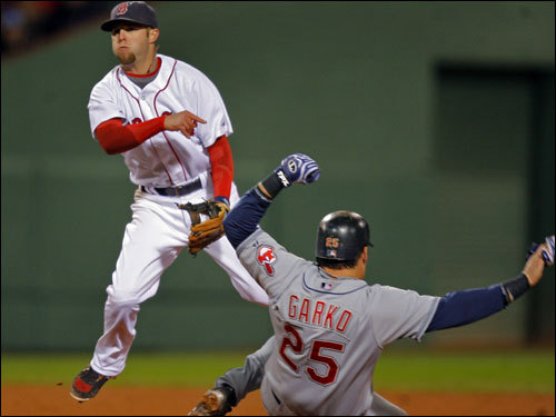 Dustin Pedroia turned a doubleplay, throwing over Ryan Garko (right) in the fifth inning.