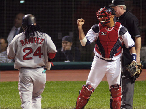 Manny Ramirez (left) jogged toward the plate as Indians catcher VIctor Ramirez (right) celebrated the second straight doubleplay to end an inning in the second inning.