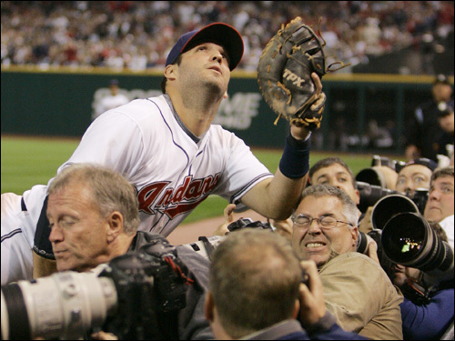 Cleveland Indians first baseman Ryan Garko goes into the crowded photographers' pit, but couldn't corral a foul pop.