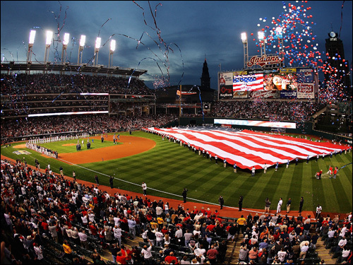 A gigantic flag is draped across center field before the game.