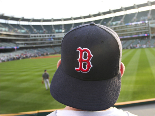 A Red Sox fan looks on from the outfield during batting practice.