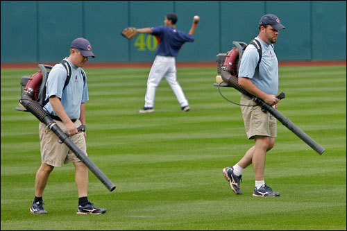 Before Game Four of the ALCS at Jacob's Field, grounds crew workers blew the water from the day's rains off the grass.