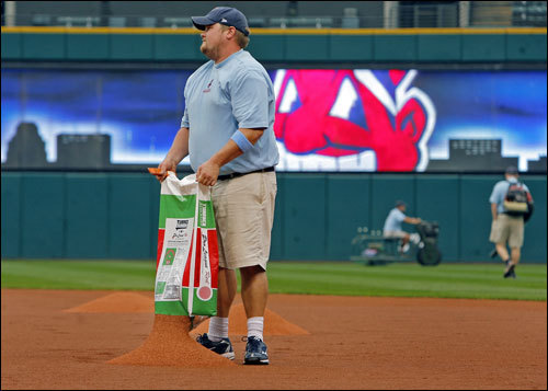 Before Game Four of the ALCS at Jacobs Field, grounds crew workers put down some dry infield dirt, as well as blew water of the field to try and get it ready following the day's rains.