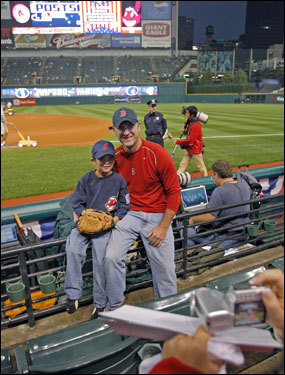 Before Game Four of the ALCS at Jacob's Field, Red Sox fan Don Shea (right) and his seven year old Indians fan son Colin (left) gave another fan their camera so they could pose for a souvenir photo with the field behind them. The Sheas are from Virginia, and Colin is an Indians fan because that's the name of his Little League team.