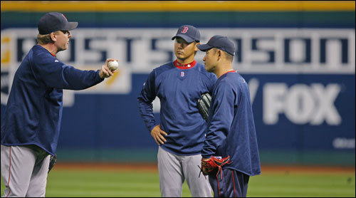 Perhaps trying to lend a hand to the struggling number three starter and his postseason woes, before Game Four of the ALCS at Jacobs Field, Red Sox veteran pitcher Curt Schilling (left) spent considerable time in the outfield talking to and demonstrating some pitching techniques to rookie Daisuke Matsuzaka (center) through an interpreter (right).