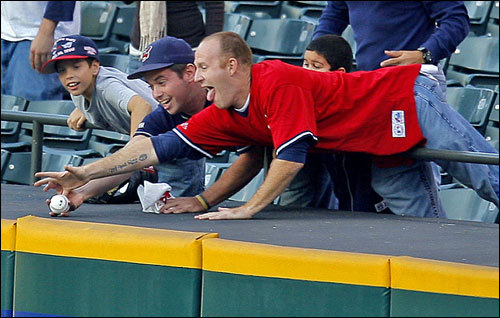 Fans in the right field bleachers battle for a ball tossed to them by an Indians player.