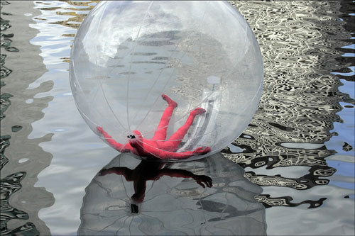 At left, an inflatable model encased in a plastic bubble floated in the Fort Point Channel. The object is part of an art exhibit by Lisa Greenfield and the crew from City Water Taxi called 'Walking On Water,' which celebrates an upcoming series of open studios for Fort Point artists.