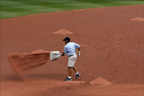 A grounds crew member at Cleveland's Jacobs Field spread dirt and prepared the field for the night's game.