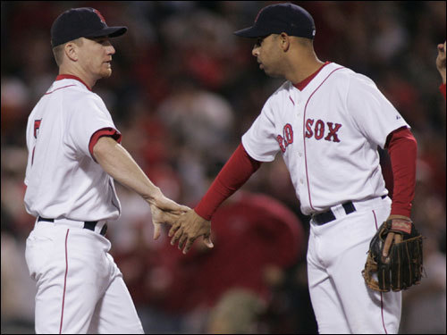 J.D. Drew (left) and Alex Cora (right) celebrated after the game.