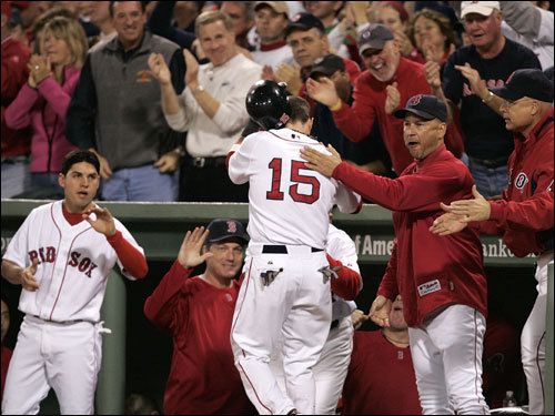 Dustin Pedroia (15) celebrated with teammates and coaches in the dugout.