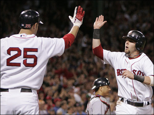Mike Lowell (left) and Dustin Pedroia (right) celebrated the Red Sox score in the first inning.