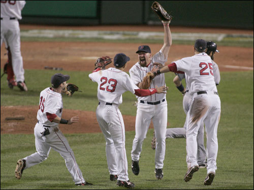 The Red Sox infield consisting of Dustin Pedroia (left), Julio Lugo (23), Kevin Youkilis (center), and Mike Lowell celebrated the Red Sox victory.