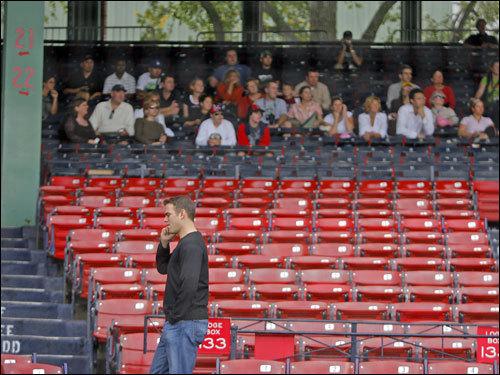 Red Sox general manager Theo Epstein, his ever present cell phone at his ear, walked through the stands past a tour group listening to the guide's stories in the grandstand along the thirdbase line.