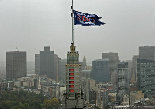John Coyne, flag coordinator at Fenway Park, and two colleagues scaled the antenna atop the Hancock with a replica of the pennant three times the size of the flag the Red Sox won Sunday night. It took four hours today and plenty of 1/4-inch-thick steel cable to hang the blue flag, which is 20 feet high and 30 feet wide.