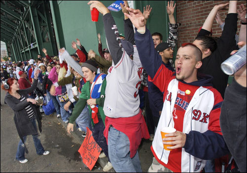 Boston Red Sox fans, including Mike Mooney (right) of Malden, Mass., react as they wait in line for vouchers for tickets to Game 1 of the World Series.