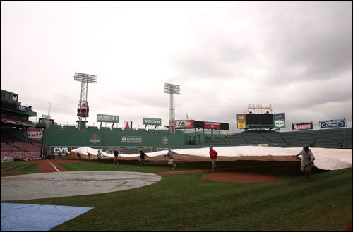 Members of the grounds crew pull a tarp over the infield prior to Game 1 of the World Series.