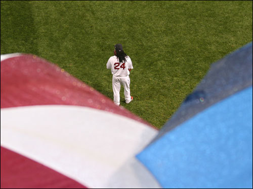 The senior Manny Ramirez was in his left field position as raindrops caused umbrellas to go up on the Monster.