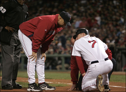 Red Sox manager Terry Francona and a trainer checked on J.D. Drew near home plate.