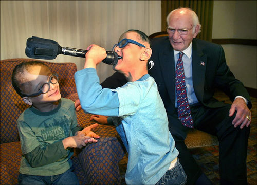 Philanthropist Ray Tye was amused by the antics of Mohammed Ibrahim Gad, 6, (left) and his Siamese twin brother, Ahmed, as they took turns singing into a television crew's microphone. Tye helped pay for the cost of separation surgery in 2003.