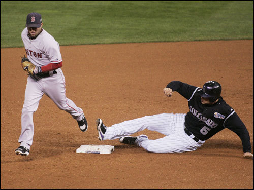 The Rockies Matt Holliday slid into second base but not in time to beat Dustin Pedroia (left) who stepped on the bag to end the first inning.