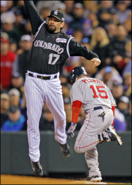 Dustin Pedroia (15) beat out the throw to Todd Helton (left) who was pulled off the bag.