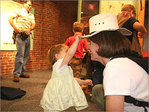 The museum hosts traveling exhibits, like 'Joshua's Journey,' where visitors can follow cowboy Joshua Loper's adventures on the Chisholm Trail. Anna, 17 months, and her mom, Mary, of Back Bay, tried on hats and vests. Visitors can also saddle up a horse and take a turn on the bucking bronco. The exhibit will be on display through January 2008.