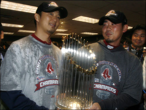 Japanese pitchers Hideki Okajima (left) and Daisuke Matsuzaka (right) held the World Series trophy during celebrations.