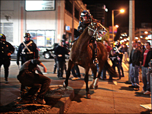 A mounted police officer near a man on Boylston Street near Fenway Park.