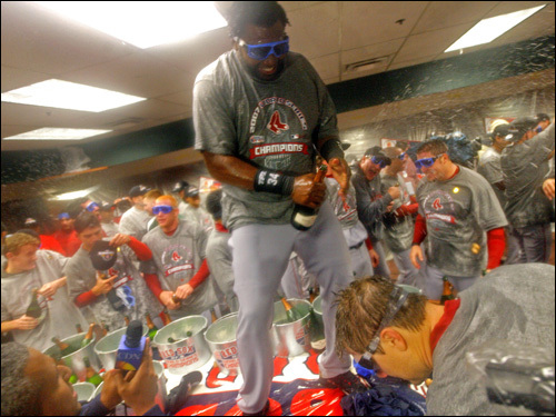 Standing on a table, David Ortiz opened a bottle of champagne.
