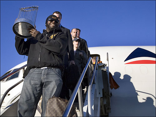 Ortiz lugged the World Series trophy down the stairs of the plane.