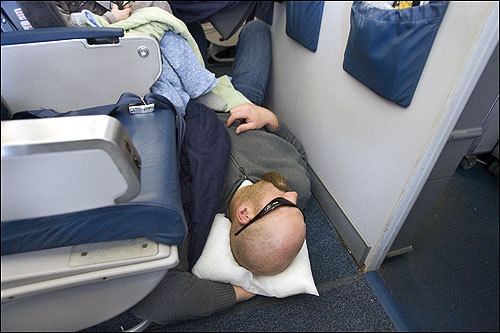 They could hardly be considered first-class accommodations, but first baseman Kevin Youkilis found an unusual spot to stretch out and catch some shut-eye across the floor of the bulkhead Row 18.