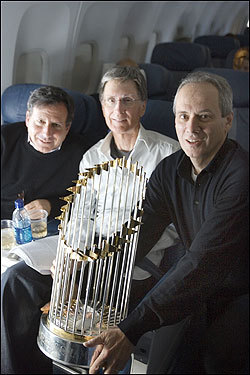 Red Sox chairman Tom Werner, principal owner John Henry and president Larry Lucchino sat with the World Series trophy on the flight home.