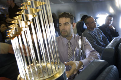 Sox third baseman Mike Lowell holds both the World Series trophy and his MVP trophy on the charter back from winning the World Series in Denver. Click here for more photos from the flight .