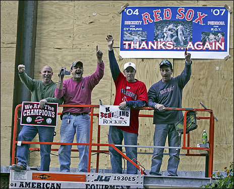 Construction workers watched the parade from a lift. Signs promoted Josh Beckett for the Cy Young Award and Dustin Pedroia for Rookie of the Year.