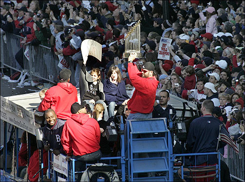 Jason Varitek holds the World Series trophy as fans cheer on Tremont Street.