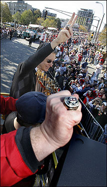 Red Sox owner John Henry waves to fans on Boylston Street. The ring belongs to vice chairman David Ginsburg.