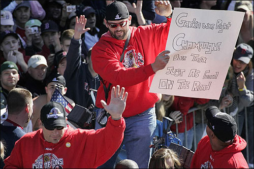 Jason Varitek held up a sign reading, 'Garko was right. Champagne does taste just as good on the road.'