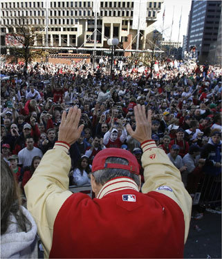 Boston Red Sox president Larry Lucchino bowed to fans at City Hall Plaza as the rolling rally passed along the parade route.