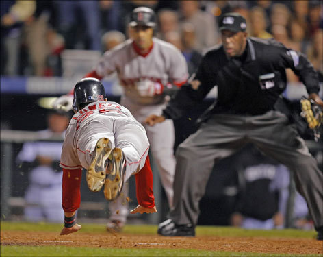 Red Sox third baseman Mike Lowell went airborne as he dived head-first and scored on Jason Varitek's fourth inning single in Game 4 of the World Series. On-deck hitter Julio Lugo and umpire Chuck Meriwether looked on in the background.