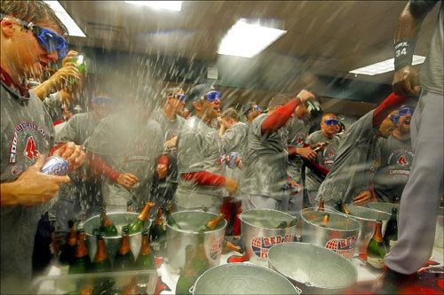 Mayhem ensued and players drenched each other in champagne in the locker room following the Red Sox World Series victory, their second title in four years.