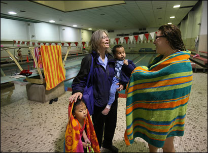 Martha Davis, (left) holds daughter Mei, 2, while she chats with swimming instructor Lauren Passariello following 5-year-old daughter Caroline's lesson. Davis is both front-line and back-up caregiver for her busy family.