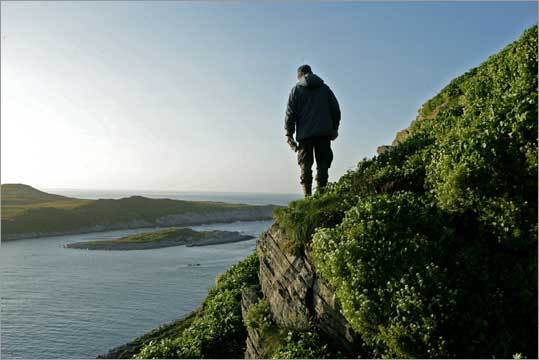 Rob Barrett looks for puffin birds' nests in the cliffs of Hornoya, Norway.
