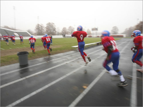 The South Boston football team bursts onto the field full of energy.