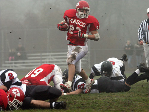 Masco's Evan Bunker seems to be the only one on his feet as he carries the ball during the first quarter.