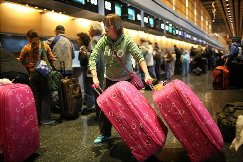 Tracey Byrne of Ireland lugged her bags all around Terminal E at Boston Logan International Airport on Nov 18. Byrne was visiting Boston with friends for the holidays.