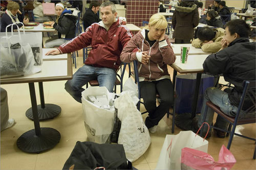 Derek Finnegan (center) and Alice Kinsella rested in the food court while surrounded by their purchases, as well as other customers.