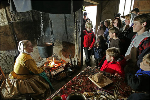 Sybregje Palenstijn (left), who plays Sarah Godbertson at Plimouth Plantation, taught visitors how to roast a turkey on a spit. The plantation often sees a large influx of visitors during the holiday season.