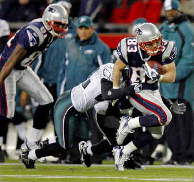 Patriots wide receiver Wes Welker fought for extra yardage after a fourth-quarter catch. The Eagles' Joselio Hanson defended; Randy Moss is at far left.
