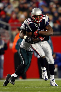 The Eagles' Lito Sheppard tackled Patriot Randy Moss (front) at Gillette Stadium.